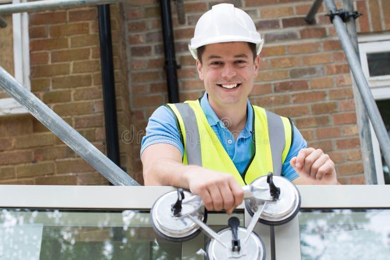 Retrato de novas janelas de Preparing To Fit do trabalhador da construção fotos de stock royalty free