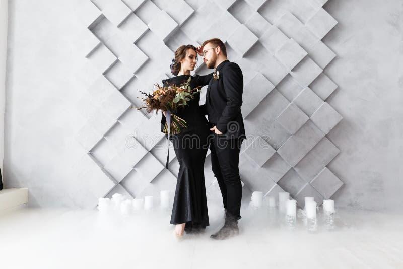 Retrato de novia y del novio en estudio Aislado en fondo geométrico gris Humo del hielo seco en piso imágenes de archivo libres de regalías