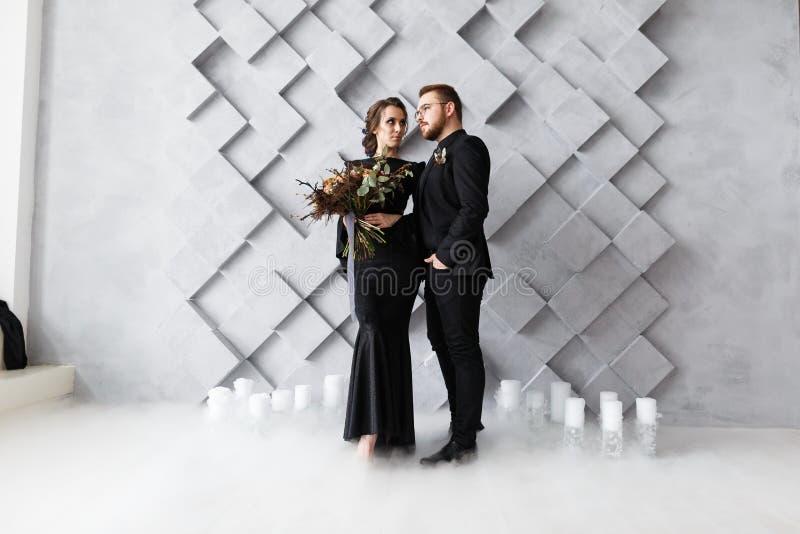 Retrato de novia y del novio en estudio Aislado en fondo geométrico gris Humo del hielo seco en piso fotografía de archivo libre de regalías