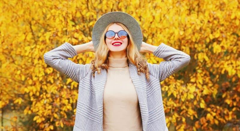 Retrato de outono, mulher feliz sorrindo divertindo-se vestindo casaco cinza, chapéu redondo com folhas amarelas imagem de stock royalty free
