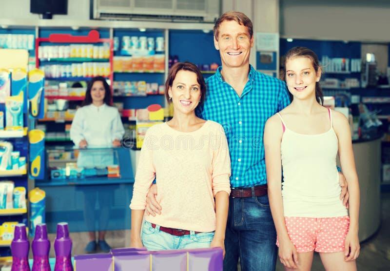 Retrato de padres con compras del adolescente de la hija en stor de la droga imagen de archivo