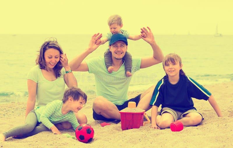 Retrato de padres sonrientes y de sus niños en la arena imagenes de archivo