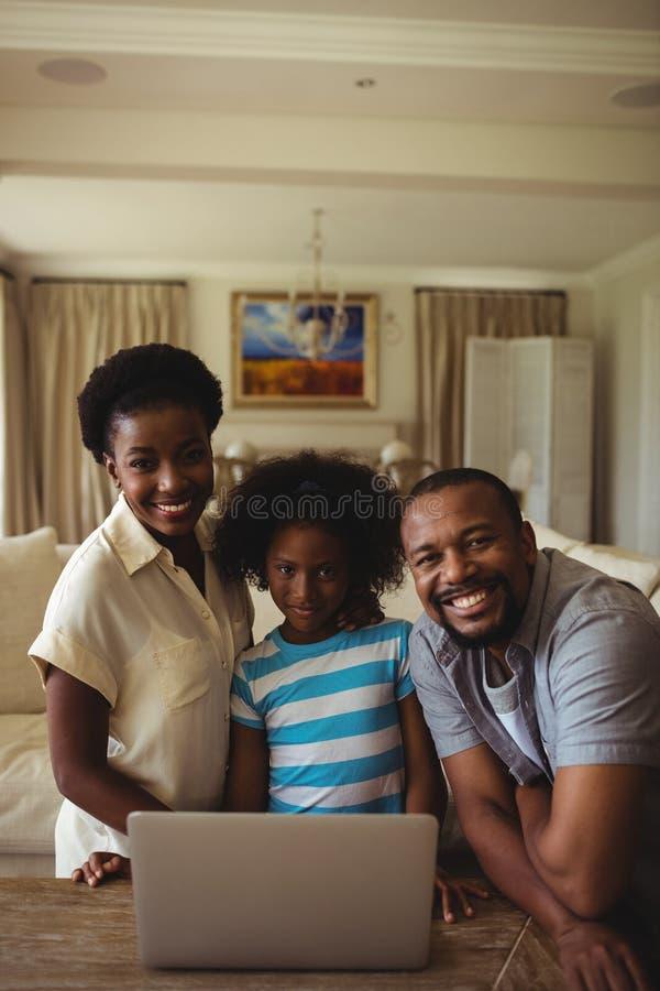 Retrato de padres y de la hija que usa el ordenador portátil en sala de estar fotografía de archivo