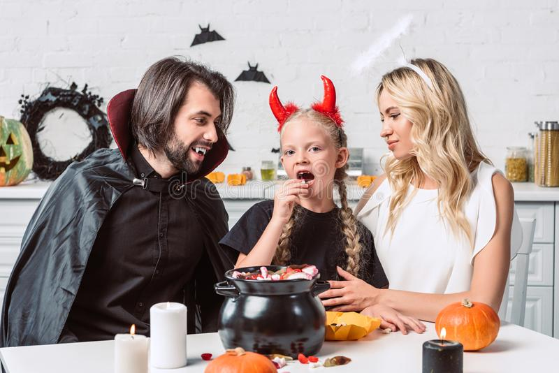 retrato de padres y de la hija en disfraces de Halloween en la tabla con las invitaciones en pote negro en cocina imágenes de archivo libres de regalías