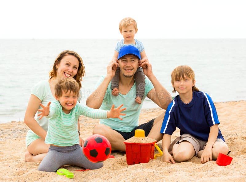 Retrato de pais felizes e de suas crianças na areia fotografia de stock