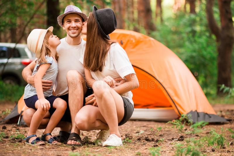 Retrato de pais novos bonitos e sua de filha pequena bonito que abra?am, olhando a c?mera e o sorriso fotografia de stock royalty free