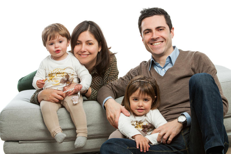 Pais novos com os miúdos no sofá. imagem de stock