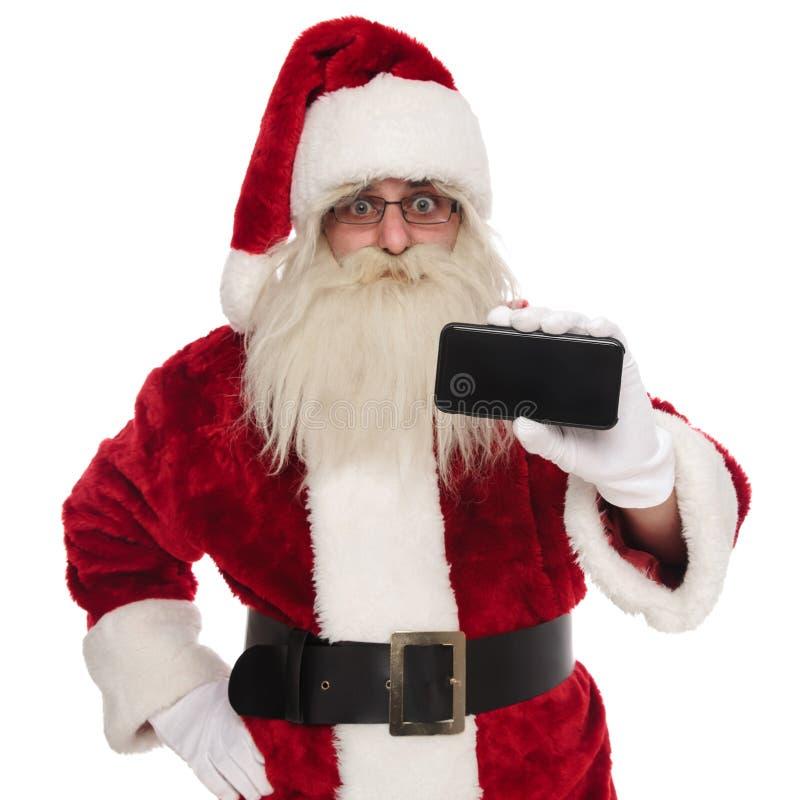 Retrato de Papá Noel que presenta la pantalla en blanco del teléfono imagenes de archivo