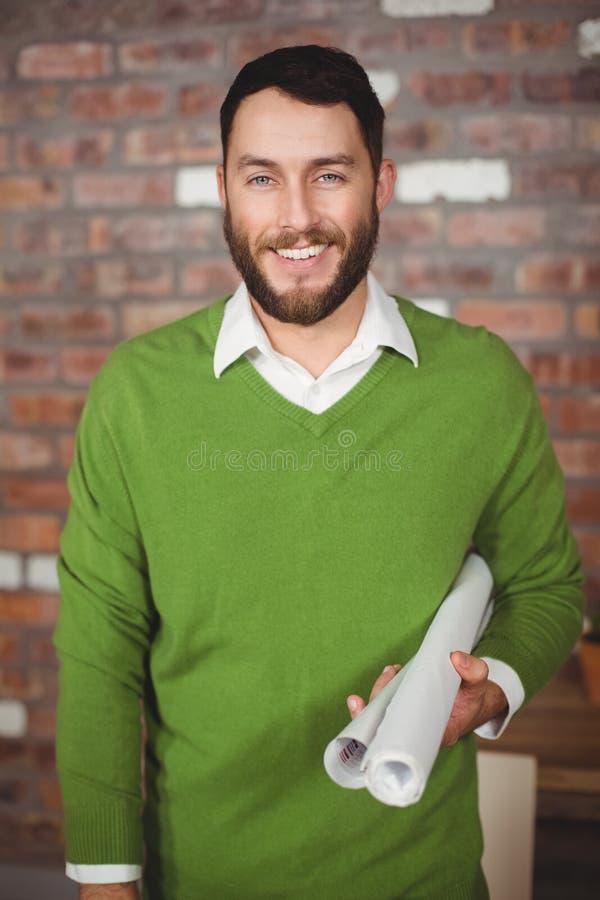 Retrato de papéis dobrados do homem de negócios terra arrendada feliz fotografia de stock