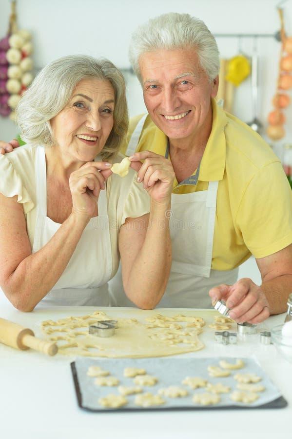 Retrato de pareja mayor horneando en la cocina en casa fotografía de archivo libre de regalías