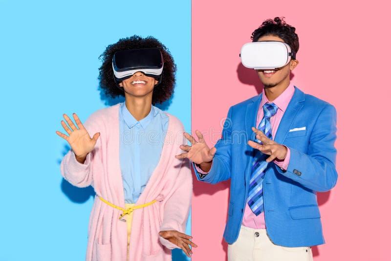 retrato de pares afro-americanos em auriculares do vr contra o rosa e o azul foto de stock