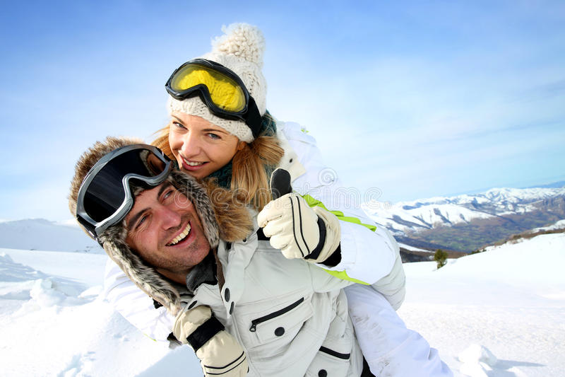 Retrato de pares alegres en las montañas nevosas imagen de archivo libre de regalías