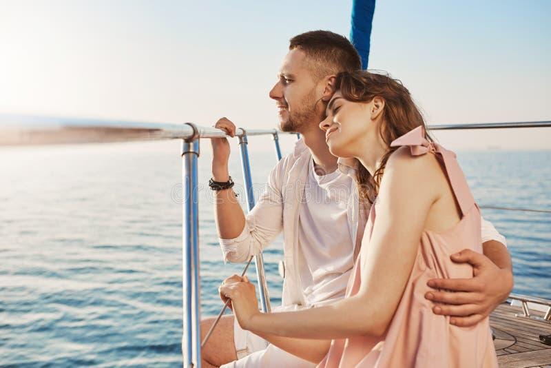 Retrato de pares elegantes en amor, abrazando mientras que se sienta en arco del yate privado y disfruta de la vista del mar El m fotografía de archivo