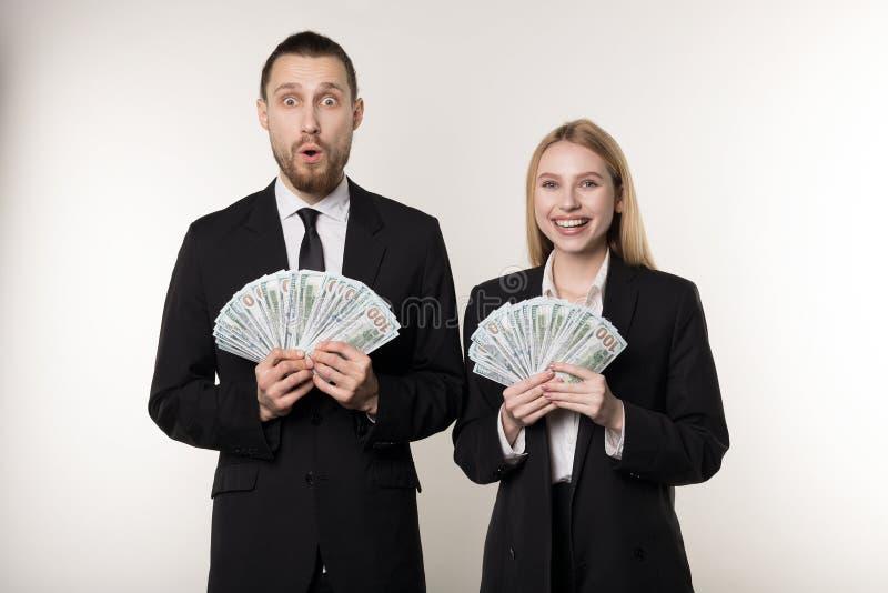 Retrato de pares en los trajes negros chocados sosteniendo billetes de banco del dinero en manos fotos de archivo libres de regalías