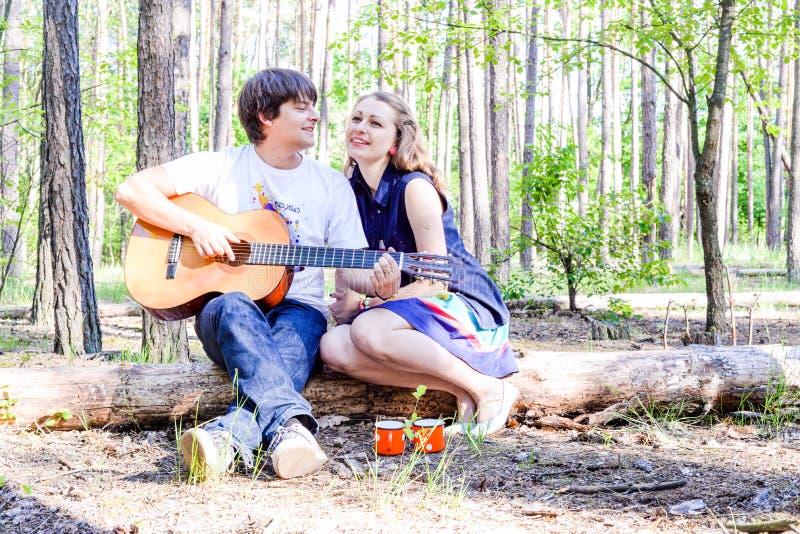 Retrato de pares felices cariñosos jovenes con la guitarra en bosque fotos de archivo