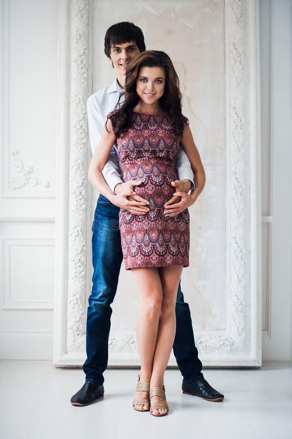 Retrato de pares felizes em casa Homem e mulher gravida imagem de stock royalty free
