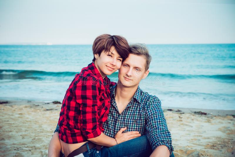 Retrato de pares felizes na praia Homem novo e mulher que sentam-se na costa arenosa e no aperto Conceito de momentos felizes dos imagens de stock