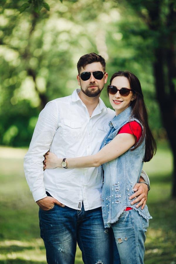 Retrato de pares felizes novos no amor, sorrindo e abraçando no jardim fotografia de stock royalty free