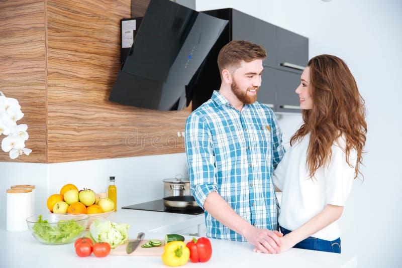 Retrato de pares jovenes felices en la cocina fotos de archivo libres de regalías