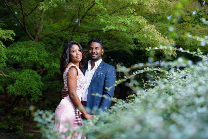 Retrato de pares jovenes felices en un jardín con follaje hermoso fotografía de archivo libre de regalías