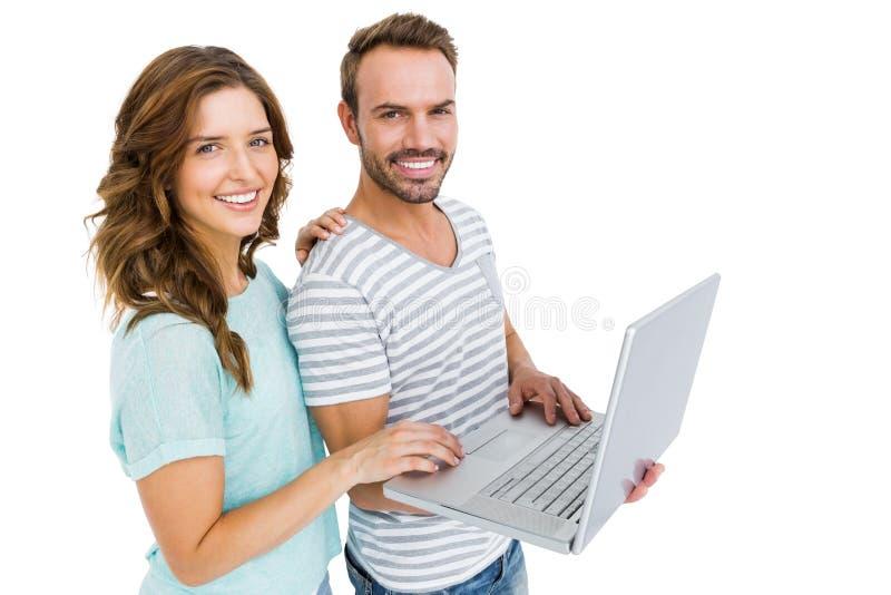 Retrato de pares jovenes felices usando el ordenador portátil foto de archivo libre de regalías