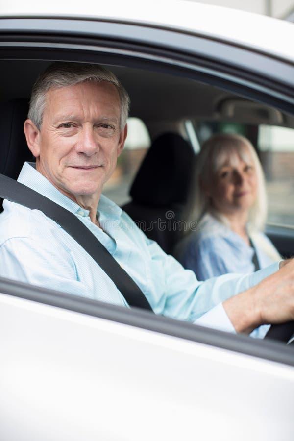 Retrato de pares maduros de sorriso na viagem do carro junto imagem de stock