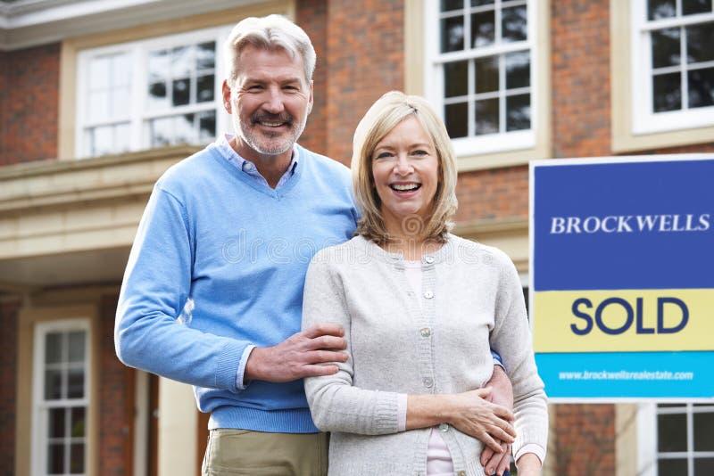 Retrato de pares maduros fora da casa nova que está pelo sinal vendido imagem de stock royalty free