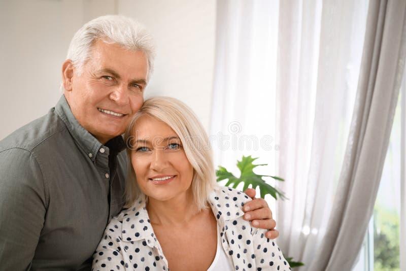 Retrato de pares mayores cariñosos en casa imagenes de archivo