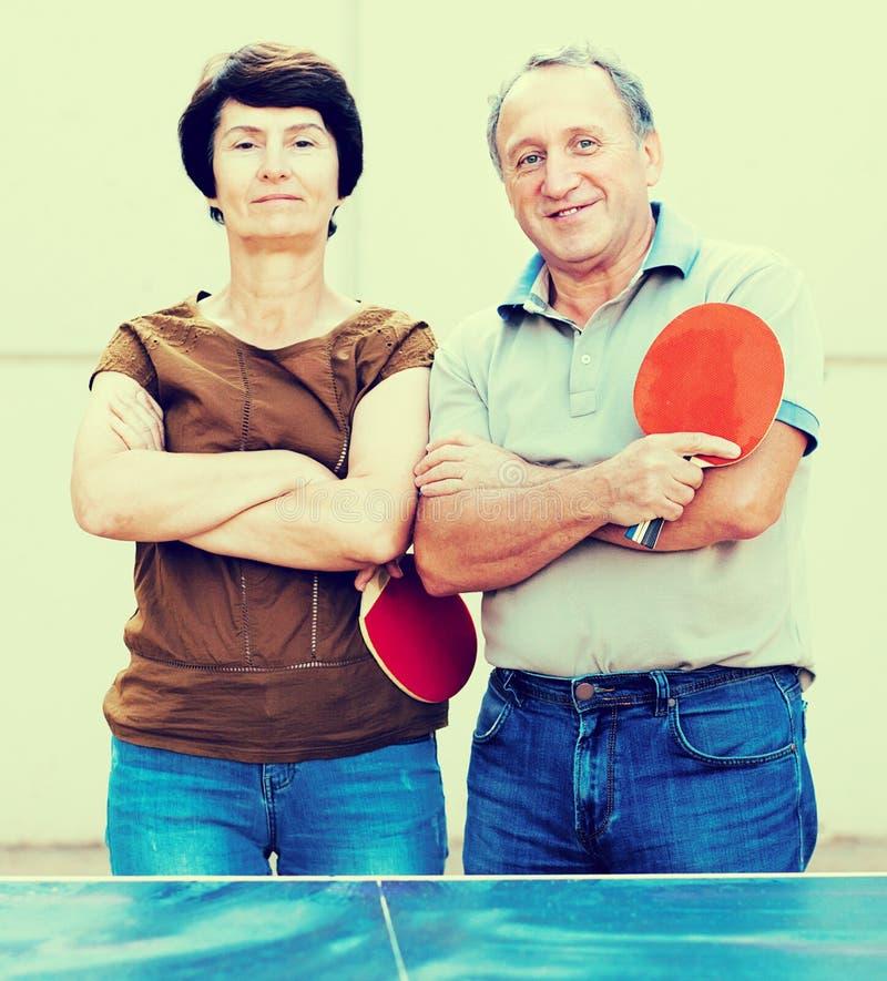 Retrato de pares mayores con las estafas para los tenis de mesa fotografía de archivo libre de regalías
