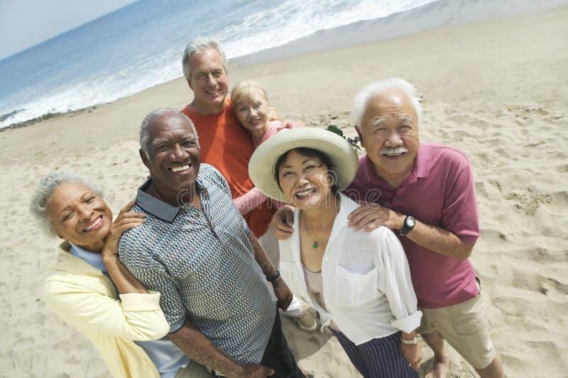 Retrato de pares multiétnicos en la playa imagenes de archivo