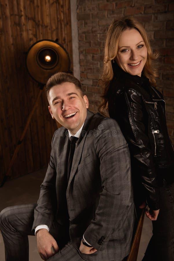 Retrato de pares novos bonitos no terno e casaco de cabedal que abraça e que sorri fotos de stock royalty free