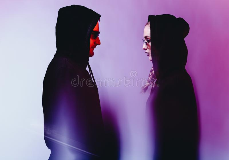 Retrato de pares novos da forma em uma camiseta preta com uma capa e os óculos de sol na luz de néon no estúdio fotos de stock