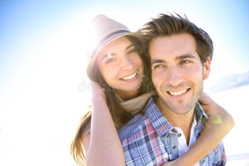 Retrato de pares novos felizes na praia foto de stock