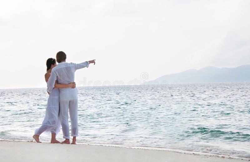 Retrato de pares novos românticos na costa de mar imagens de stock