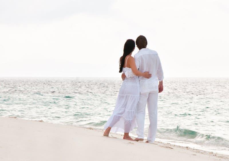 Retrato de pares novos românticos na costa de mar imagem de stock