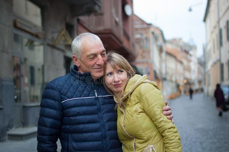 Retrato de pares rom?nticos felices con la diferencia de la edad que abraza al aire libre en la ciudad antigua durante la primave imagen de archivo libre de regalías