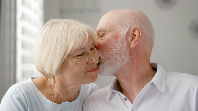 Retrato de pares sênior felizes em casa O homem superior expressa suas emoções e beija sua esposa fotos de stock royalty free