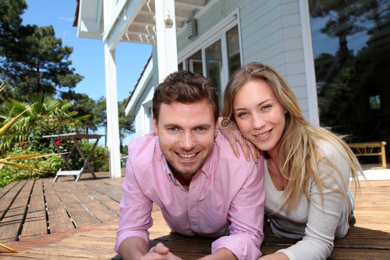 Retrato de pares sonrientes delante de su nuevo hogar fotos de archivo