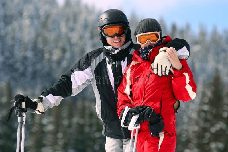 Retrato de pares sonrientes en los esquís fotografía de archivo libre de regalías