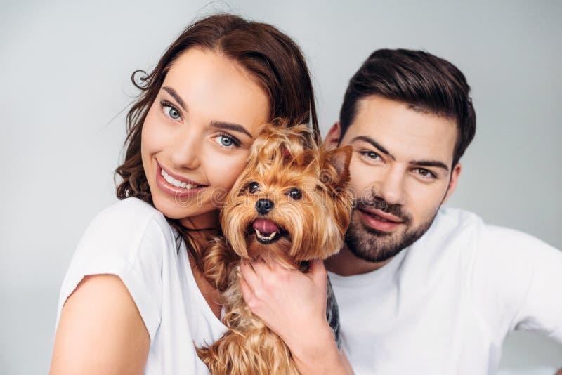 retrato de pares sonrientes jovenes con el terrier de Yorkshire que mira la cámara imagenes de archivo