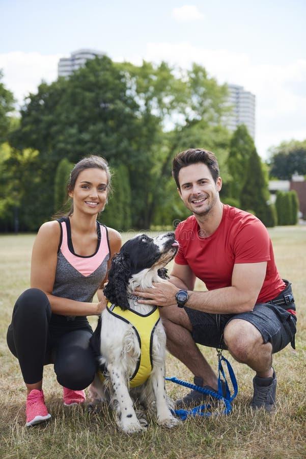 Retrato de pares sonrientes y su perro después del entrenamiento imagen de archivo