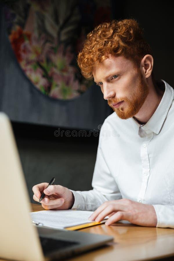 Retrato de pensar al hombre joven del readhead que mira el ordenador portátil el wor foto de archivo libre de regalías