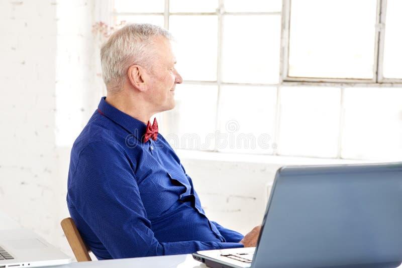 Retrato de pensar o homem de negócios superior que senta-se no escritório atrás de seu portátil fotos de stock