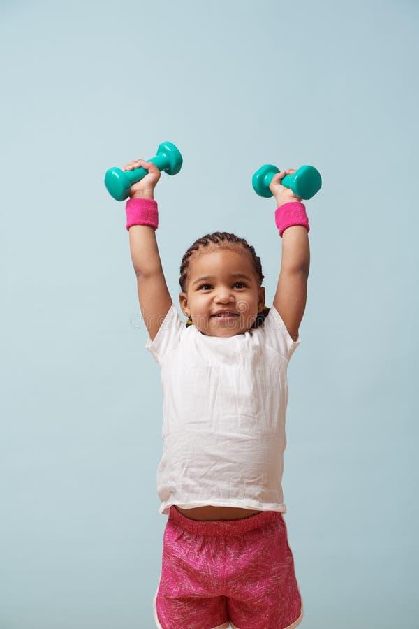 Retrato de pesos de levantamento da menina pequena bonito do mulato em cima foto de stock royalty free