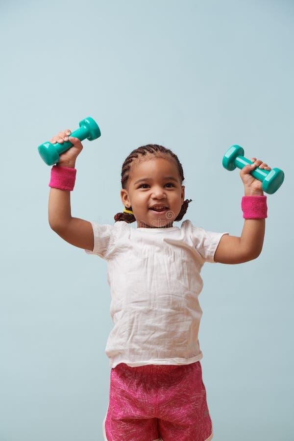 Retrato de pesos de levantamento da menina pequena bonito do mulato Empalideça - o fundo azul imagem de stock royalty free