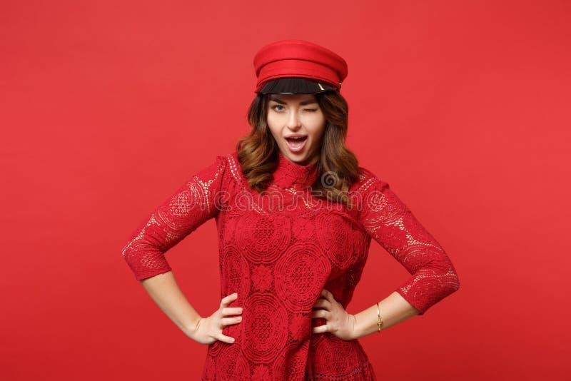 Retrato de piscar a jovem mulher alegre no vestido do laço, posição do tampão com os braços akimbo na parede vermelha brilhante fotografia de stock royalty free