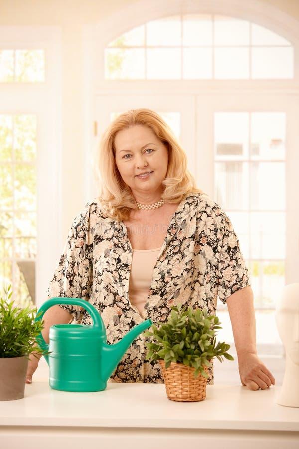 Plantas molhando da mulher em casa fotos de stock royalty free