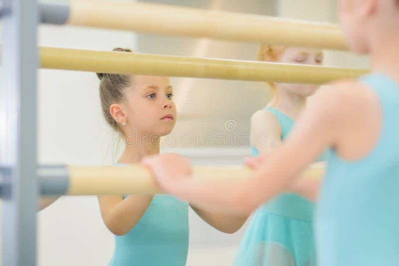 Retrato de poco ballet practicante de la bailarina en estudio cerca de la barra El estudiar en escuela de danza fotos de archivo libres de regalías