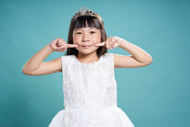 Retrato de pouca menina asiática da princesa do sorriso na coroa de prata fotografia de stock