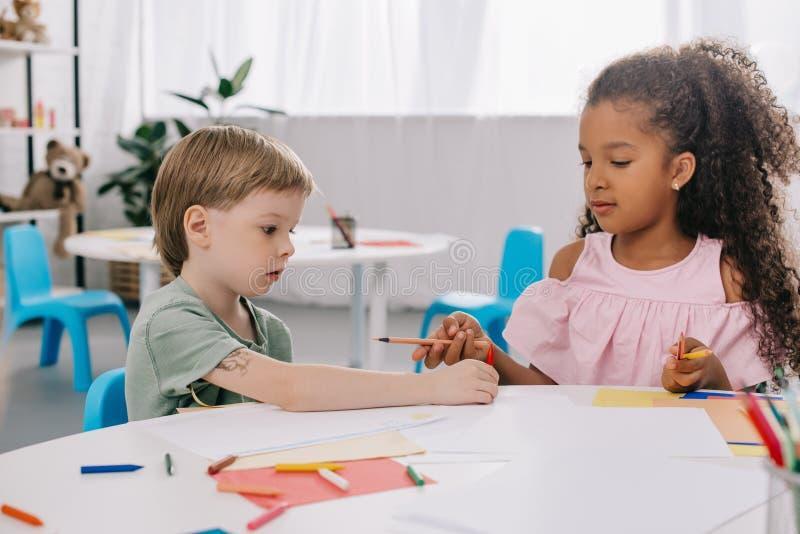 retrato de preescolares multiculturales en la tabla con los papeles y los lápices foto de archivo libre de regalías